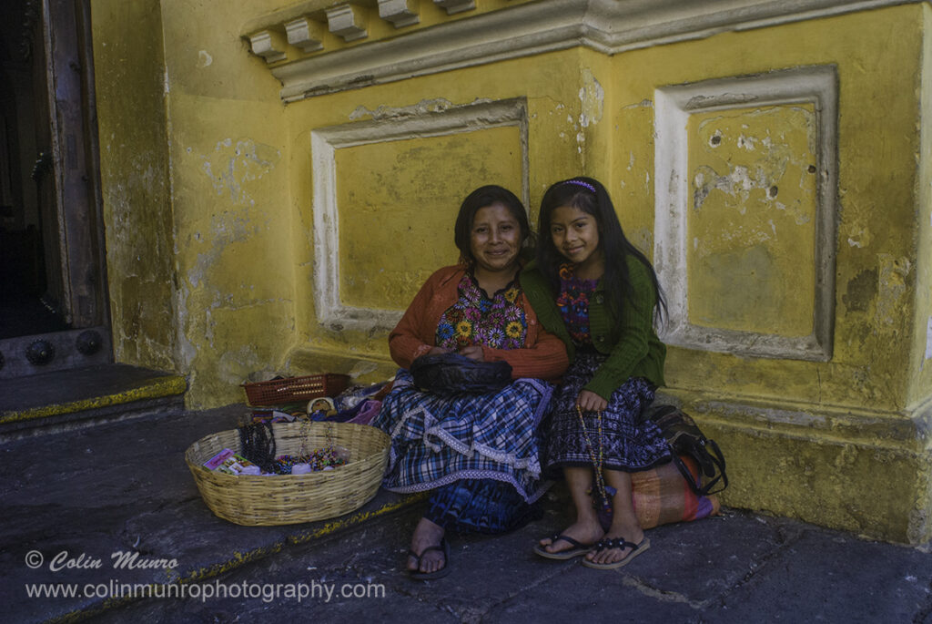 Travel photography tips. Always try to establish a relationship with your subject. A mayna mother and dauther sell hand made bead necklaces and bracelets near the catholic cathedral, La Antigua, Guatemala. Colin Munro Photography
