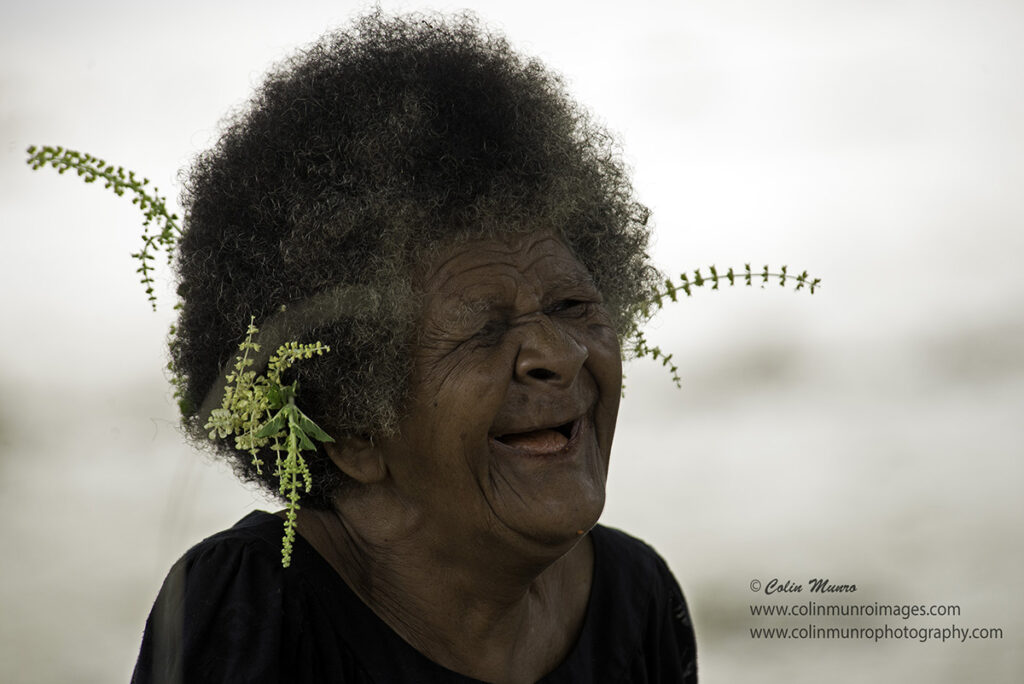 Travel Photography Tips. An old lady laughs as she weaves pandanus leaves. Suau Island, Milne Bay, Papua New Guinea. Colin Munro Photography